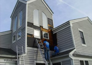 two workers replacing siding on a home that is gray